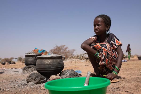 OCHA/Otto Bakano Une jeune fille devant une marmite dans un camp pour personnes déplacées à Barsalogho, dans la région du Centre-Nord, du Burkina Faso.