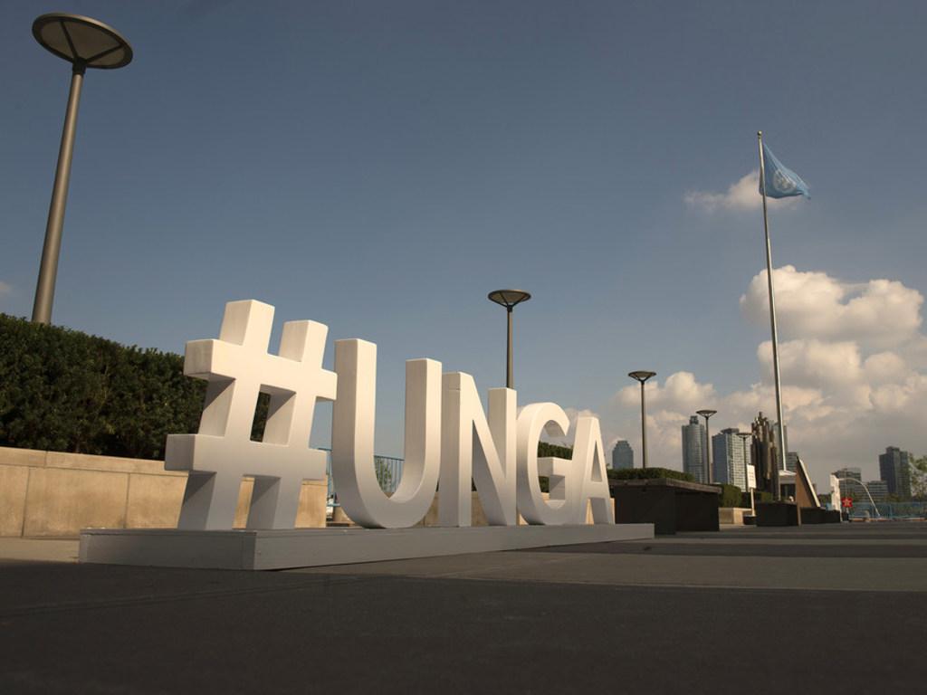 Photo ONU/Kim Haughton Devant le siège de l'ONU à New York, l'Assemblée générale des Nations Unies fait la promotion de son débat général annuel avec le hashtagh de ses acronymes en anglais (archive)