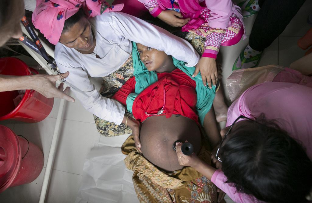 UNFPA Bangladesh/Allison Joyce Des agents de santé aident une femme enceinte au centre de maternité du camp de réfugiés de Nayapara, à Cox's Bazar, au Bangladesh